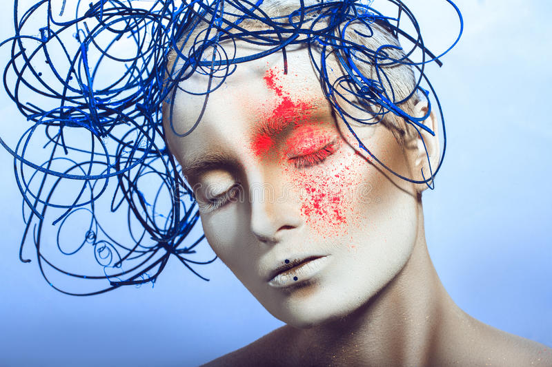Voluptuous girl with white body art and neon powder on face royalty free stock photography