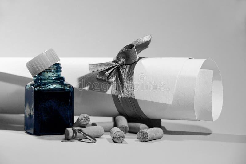 Voluta del Libro Blanco, de la botella de tinta, de tizas en colores pastel y de canillas del metal en fondo ligero foto de archivo libre de regalías