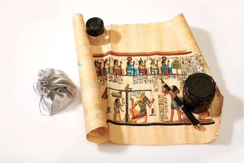 Voluta, pluma, lupa y tesoros egipcios en el bolso en un wh fotos de archivo