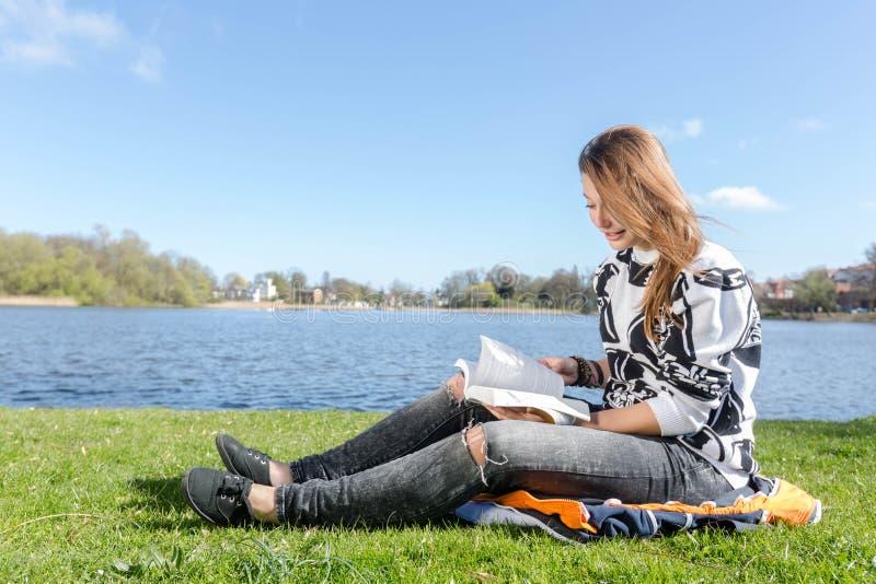 Volutas de una muchacha y lectura de un libro foto de archivo libre de regalías