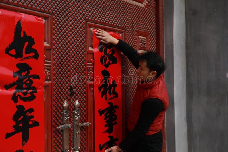 Volutas del ` s del Año Nuevo de los posts del hombre, pareados del festival de primavera y Marte chinos en la puerta roja en Chi imágenes de archivo libres de regalías