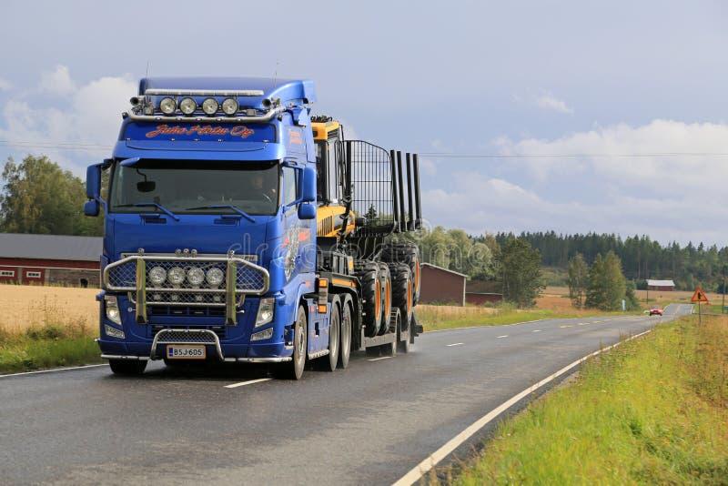 Volvo FH13 тянет товароотправителя Ponsse на дороге стоковые изображения rf