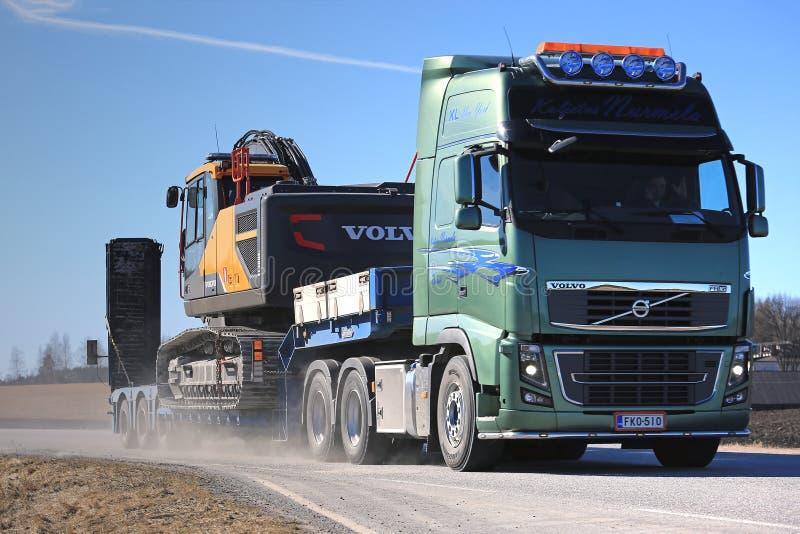 Volvo FH16 Hauls Construction Equipment Along Highway stock photos