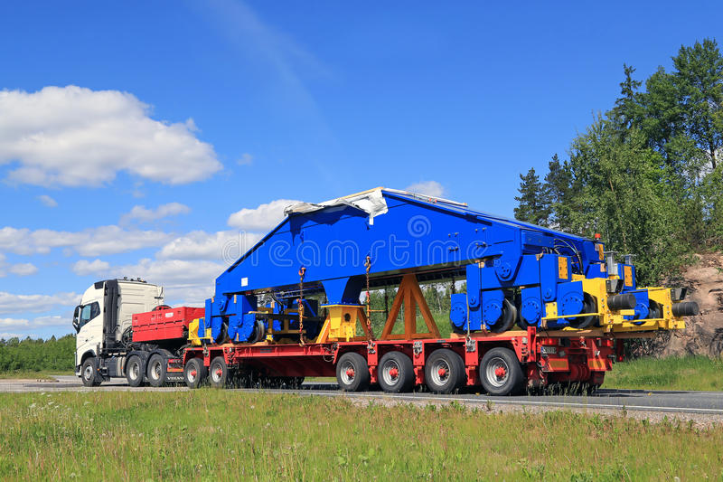 Volvo FH16 Hauls Shipyard Crane Component. PAIMIO, FINLAND - JUNE 4, 2016: White Volvo FH16 750 transports a shipyard crane bogie on trailer. The weight of the royalty free stock photo