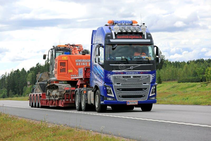 Volvo FH16 Semi Hauls Hitachi Tracked Excavator royalty free stock photos