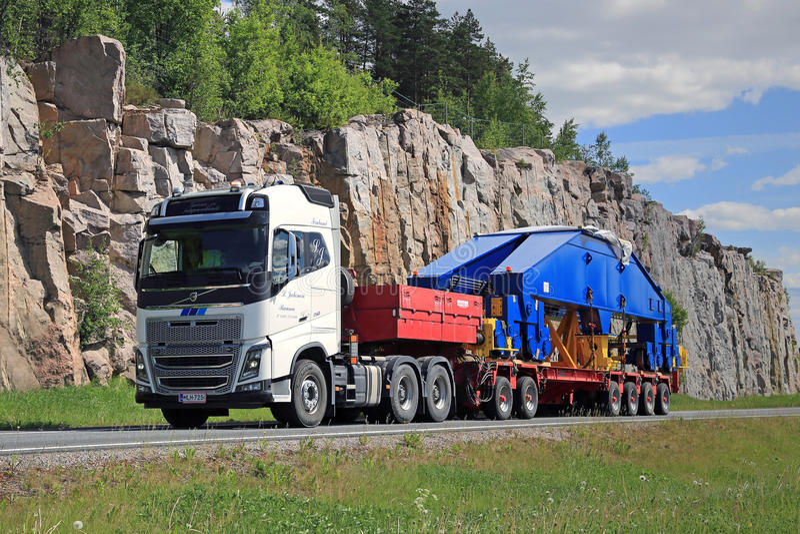 Volvo FH16 750 Semi transports Shipyard Crane Component. PAIMIO, FINLAND - JUNE 6, 2016: White Volvo FH16 750 transports shipyard crane component on trailer. The royalty free stock images