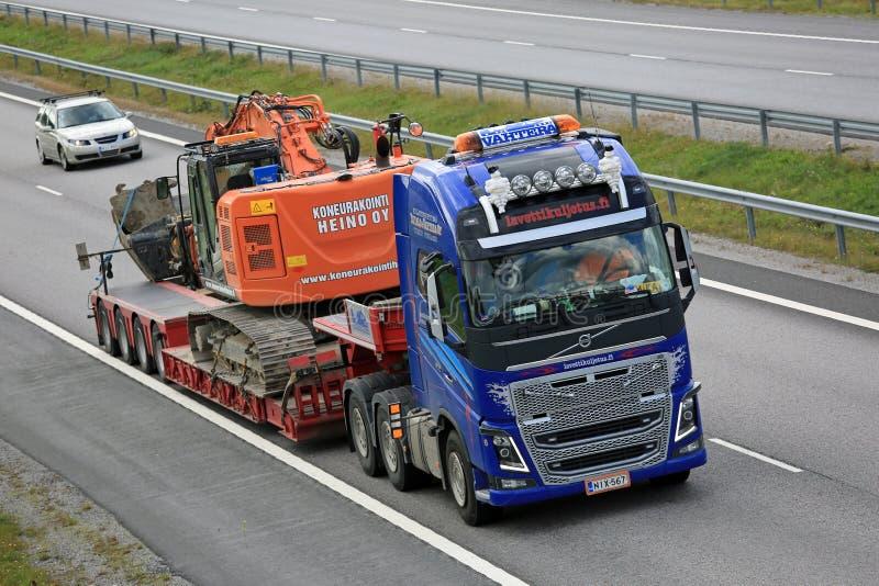 Volvo FH16 transportiert Bagger auf Autobahn lizenzfreies stockfoto