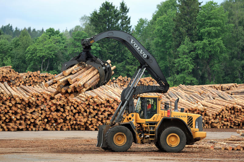 Volvo L180F HL Log Loader Handling Logs. KYRO, FINLAND - JUNE 7, 2014: Volvo L180F High Lift wheel loader working at the mill lumber yard. The arm is capable of royalty free stock image