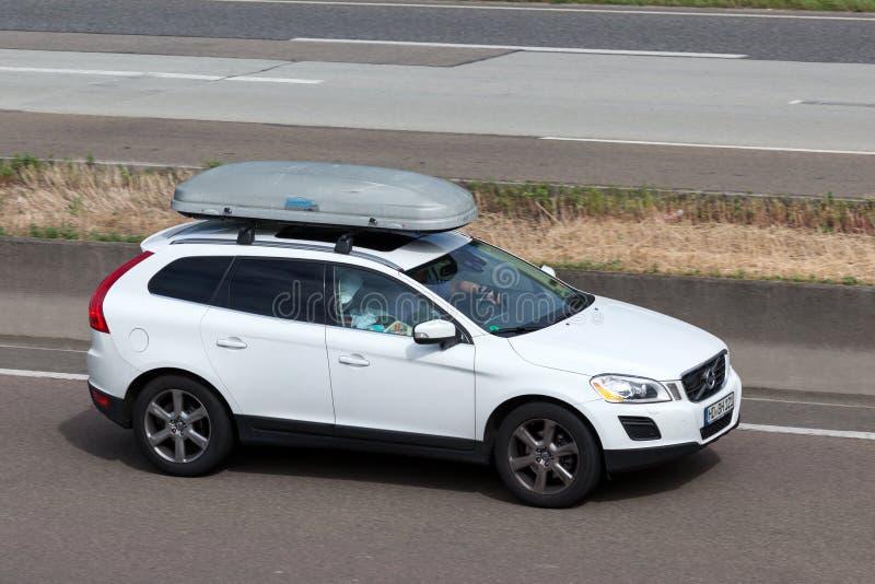 Volvo XC60 com uma caixa do telhado na estrada fotos de stock royalty free