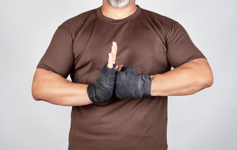 volwassen atleet in bruine kleren met het verbonden verband van handen zwarte textielsporten royalty-vrije stock foto