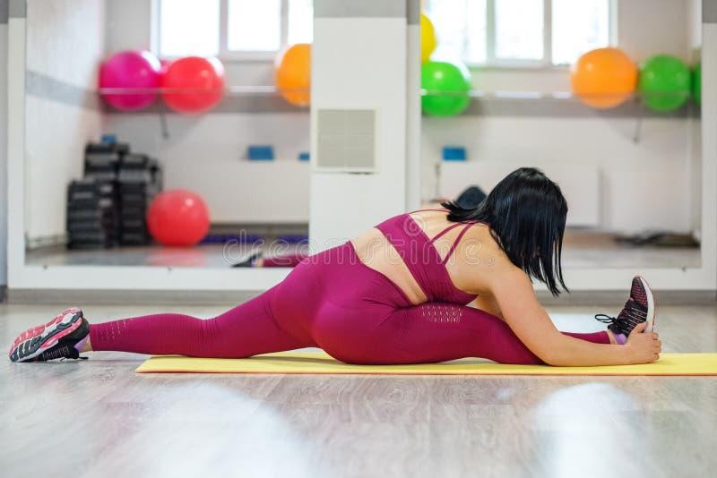 Volwassen atletisch meisje belast met zich het uitrekken in de gymnastiek Het concept sporten, een gezonde levensstijl, verliezen royalty-vrije stock fotografie