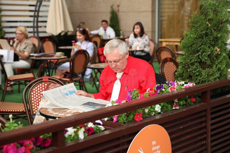 Volwassen bedrijfsmens in een koffie die een krant lezen moskou 11 07 royalty-vrije stock afbeelding