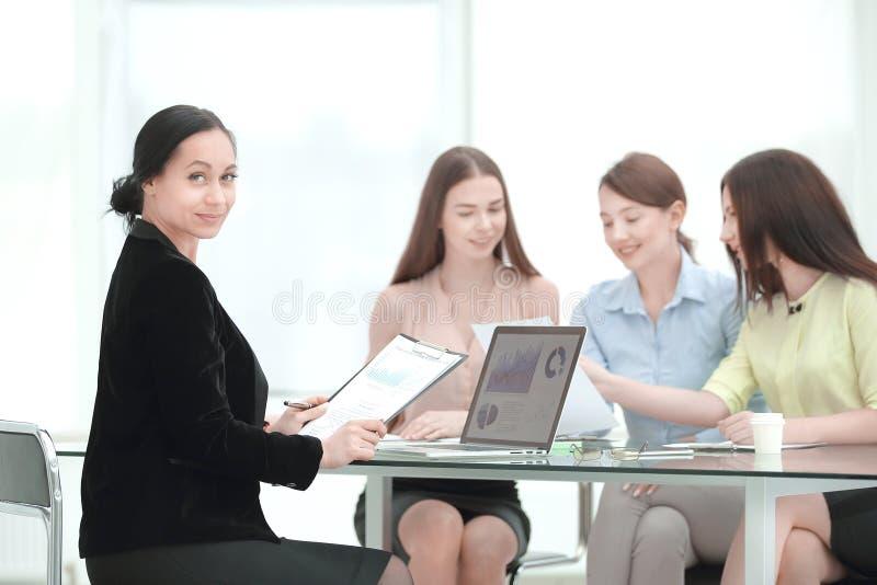Volwassen bedrijfsvrouw en groep jonge werknemers bij het werkbureau stock foto
