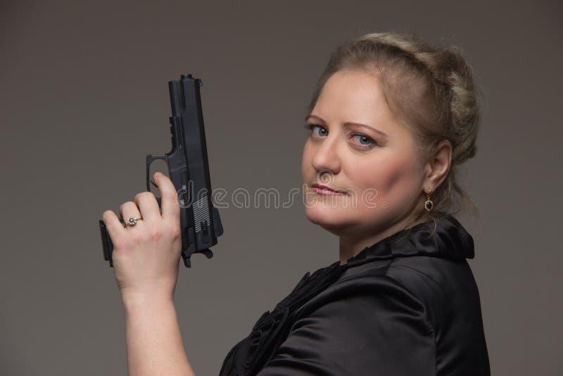 Volwassen bedrijfsvrouw met zwart kanon op een grijze achtergrond royalty-vrije stock afbeeldingen