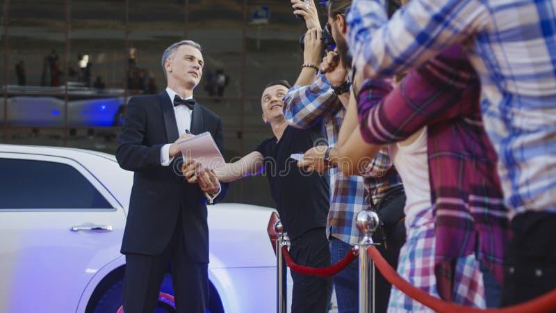 Volwassen beroemdheid die autographs op rood tapijt geven stock foto's