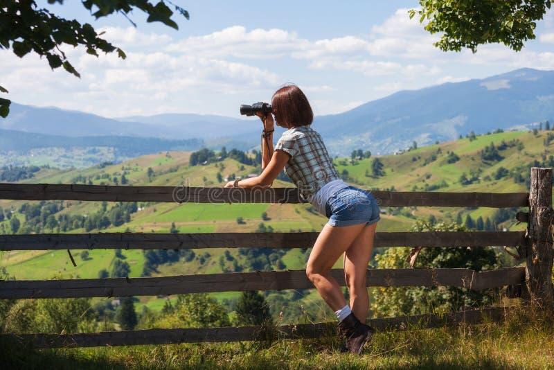 Volwassen de holdingsverrekijkers van het reismeisje stock fotografie