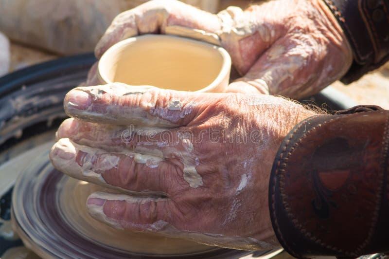 volwassen die hand de handen van de baby wordt gevoed aan het werk met een wiel van de pottenbakker royalty-vrije stock fotografie
