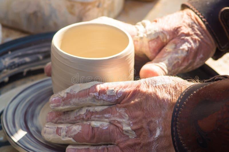 volwassen die hand de handen van de baby wordt gevoed aan het werk met een wiel van de pottenbakker royalty-vrije stock afbeeldingen
