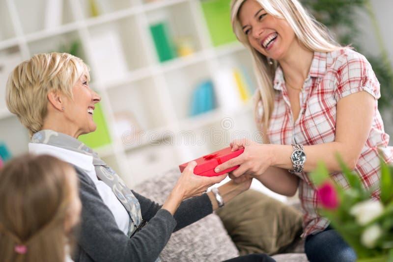 Volwassen dochter die aan haar moedergift voor Moederdag geven stock afbeelding