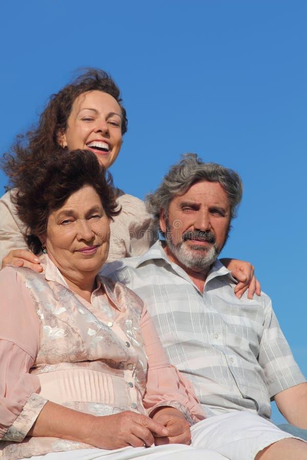 Volwassen dochter die ouders en het glimlachen omhelst stock afbeelding
