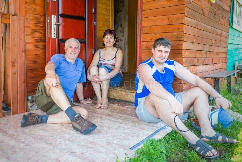 Volwassen familiezitting op de portiek stock foto's
