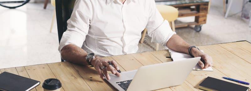 Volwassen gebaarde mens die aan mobiele laptop computer werken terwijl het zitten bij houten lijst bebouwd wijd royalty-vrije stock foto's