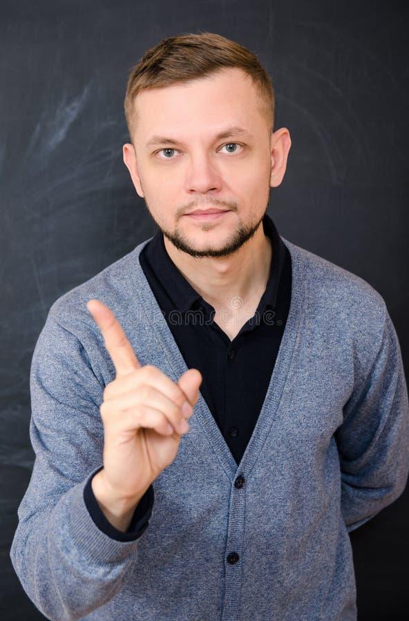 Volwassen gebaarde mens die wijsvinger tonen stock foto