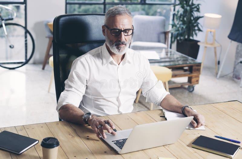 Volwassen gebaarde zakenman die aan mobiele laptop computer werken terwijl het zitten bij houten lijst royalty-vrije stock afbeelding
