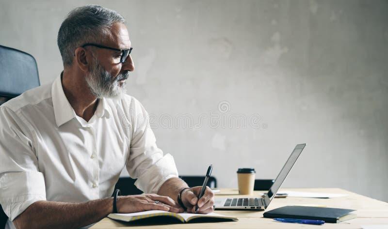 Volwassen gebaarde zakenman die aan mobiele laptop computer werken terwijl het zitten bij houten lijst stock afbeelding