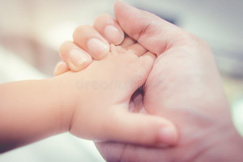 Volwassen hand die weinig babyhand houden stock afbeelding