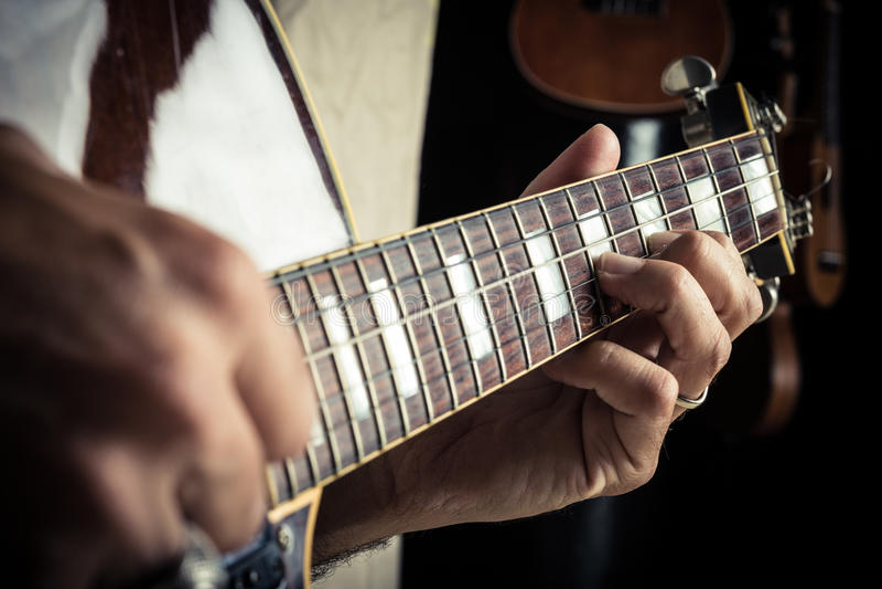Volwassen Kaukasisch gitaristportret die elektrische gitaar op grungeachtergrond spelen Sluit omhoog instrumentendetail Muziek royalty-vrije stock foto