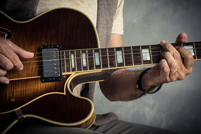 Volwassen Kaukasisch gitaristportret die elektrische gitaar op grungeachtergrond spelen Sluit omhoog instrumentendetail Muziek royalty-vrije stock foto's