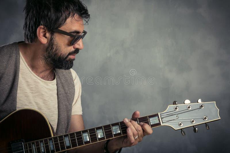 Volwassen Kaukasisch gitaristportret die elektrische gitaar op grungeachtergrond spelen Sluit omhoog instrumentendetail Muziek royalty-vrije stock afbeeldingen
