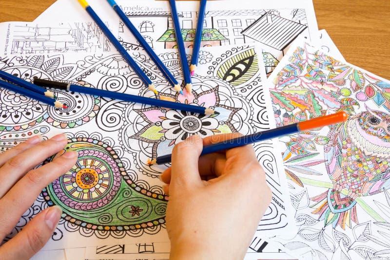 Volwassen kleuringsboeken met potloden, nieuwe spannings verlichtende tendens, de persoon van het mindfulnessconcept illustratief stock foto
