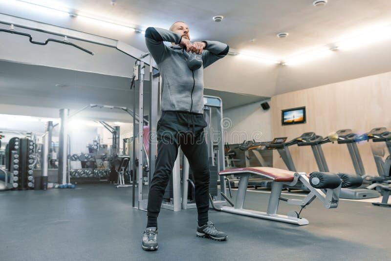 Volwassen knappe gebaarde mens die lichaamsbewegingen in de gymnastiek doen Sportrehabilitatie, leeftijd, gezond levensstijlconce royalty-vrije stock fotografie