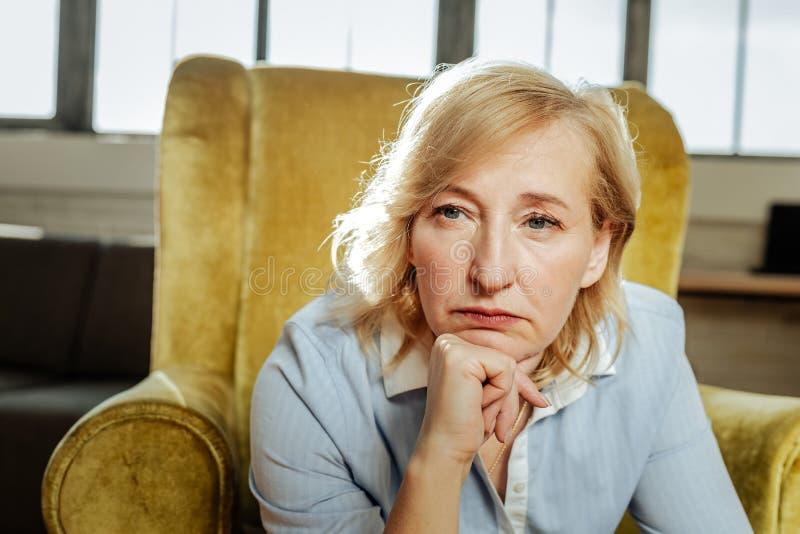 Volwassen kortharige vrouw met blauwe ogen die ongelukkig en gedeprimeerd zijn royalty-vrije stock afbeeldingen