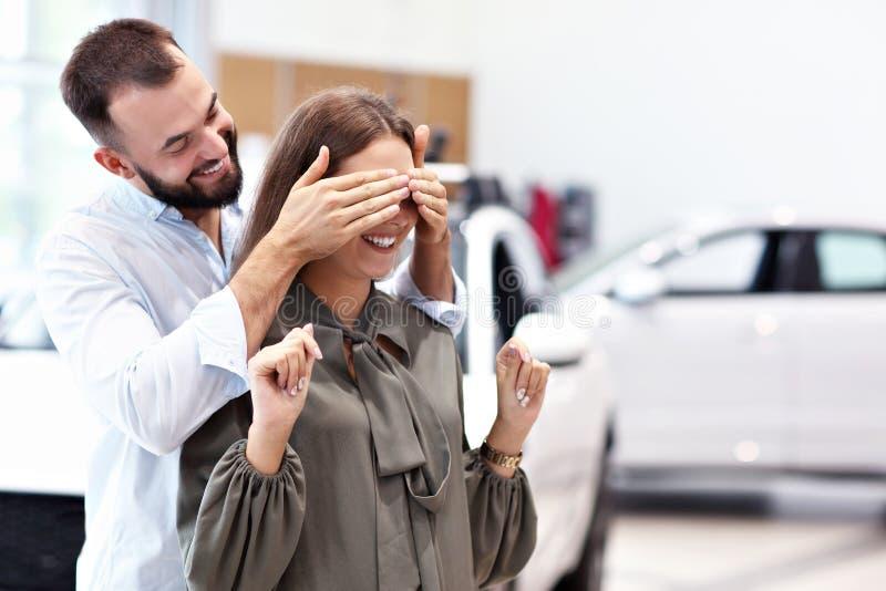 Volwassen man die tot verrassing maken aan mooie vrouw in autotoonzaal stock foto