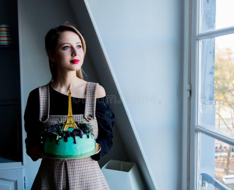 Volwassen meisje die een roomcake met de toren van Eiffel houden stock foto's