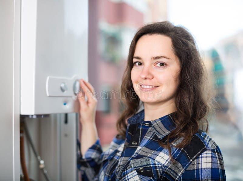 Volwassen meisje in overhemd dichtbij boilercontrolebord stock afbeelding