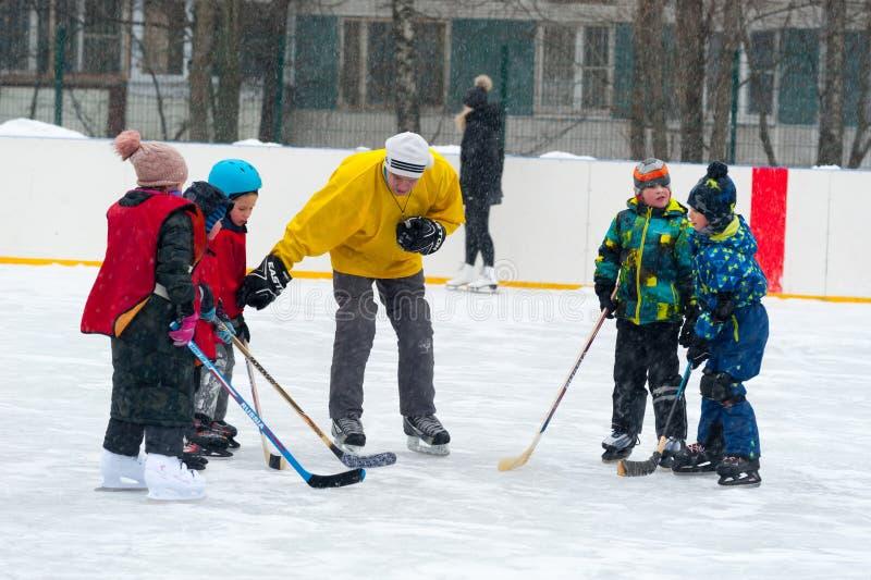 Volwassen mens die aan kinderen verklaren hoe te ijshockey 26 te spelen 11 2019 stock afbeelding