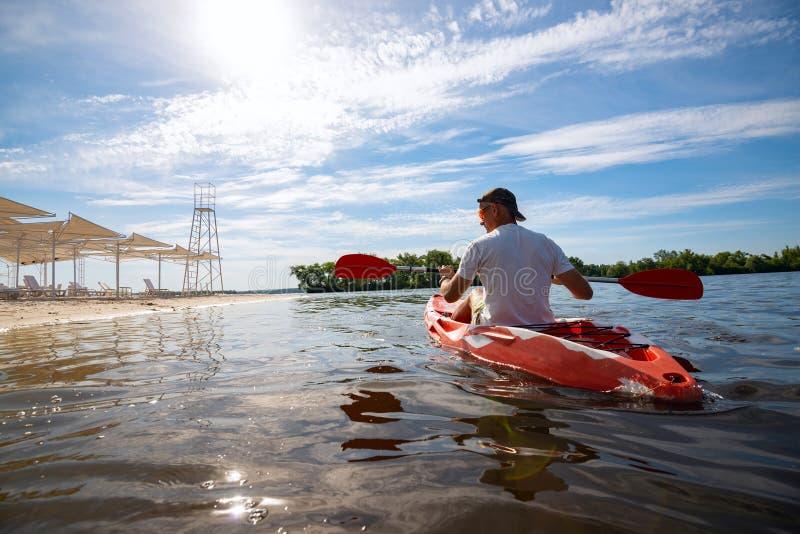 Volwassen mens die een kajak in het overzees naast het strand paddelen royalty-vrije stock foto's