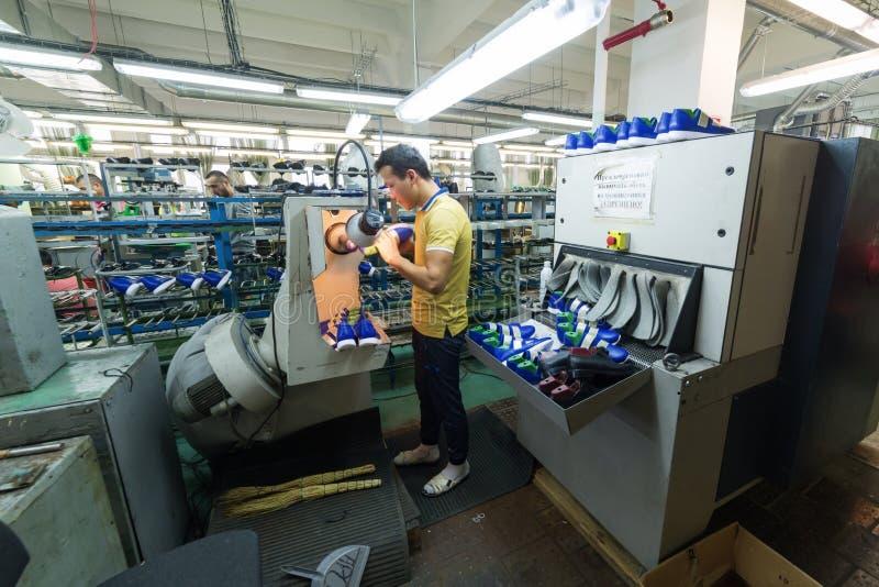 Volwassen mens die in een schoenfabriek werken, die de zolen van de schoenen beëindigen, bij een machine stock afbeelding