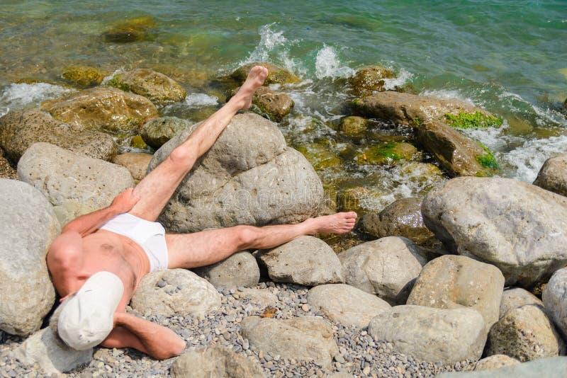 Volwassen mens die op het strand zonnebaden die op grote stenen liggen stock fotografie