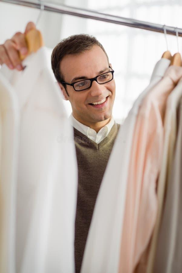 Volwassen mens die overhemd in klerenwinkel kiest royalty-vrije stock afbeeldingen