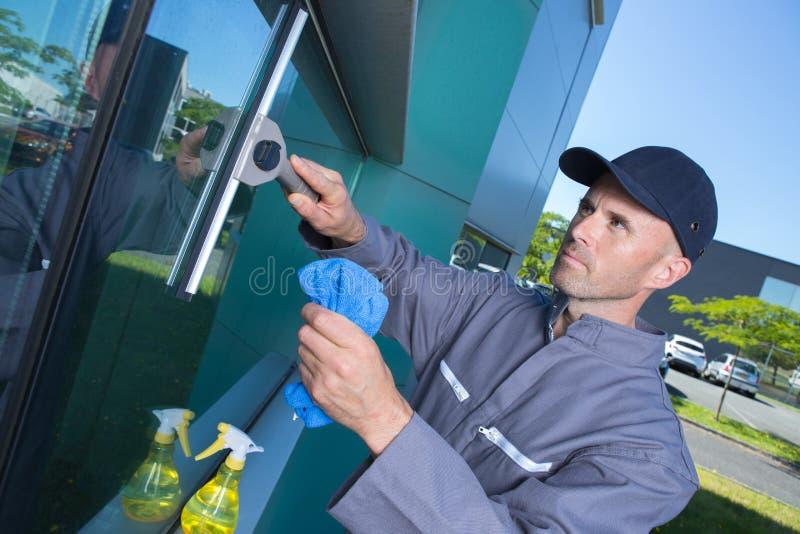 Volwassen mens die vuile vensterauto wassen stock foto