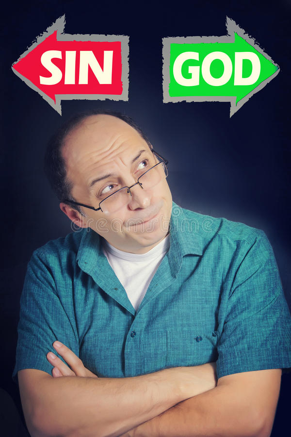 Volwassen mens die wat denken om tussen ZONDE en GOD te kiezen royalty-vrije stock foto
