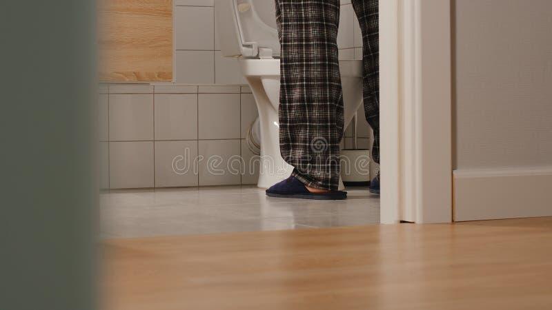 Volwassen mens in een toilet thuis stock foto