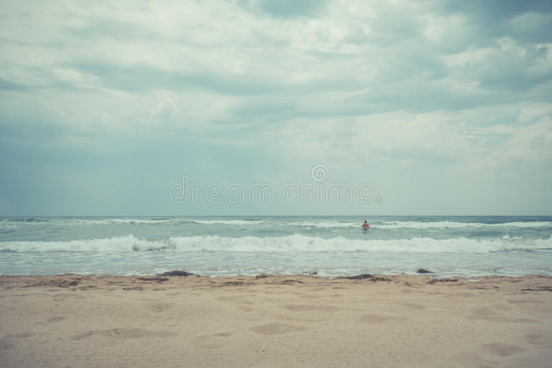 Volwassen mens in het water bij het strand op een bewolkte dag royalty-vrije stock foto's