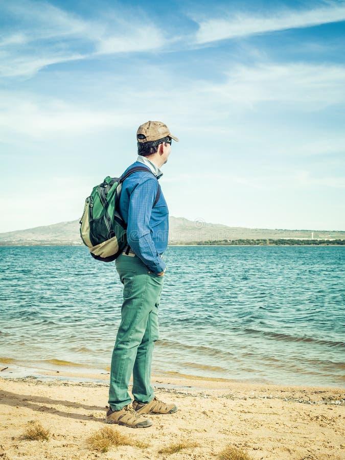 Volwassen mensenwandelaar die met backpacker de horizon op het waterreservoir bekijkt royalty-vrije stock foto