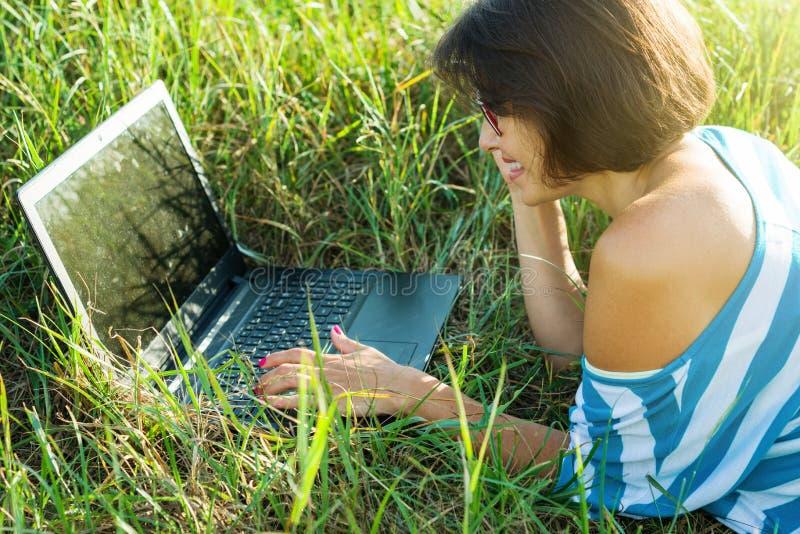 Volwassen mooie vrouw die laptop in aard, openluchtportret met behulp van royalty-vrije stock fotografie